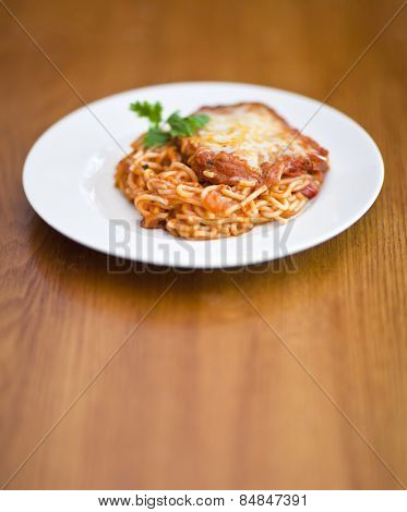 Chicken parmigiana on a white plate and wooden table
