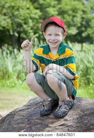 Cute boy with big smile outdoors on rock portrait