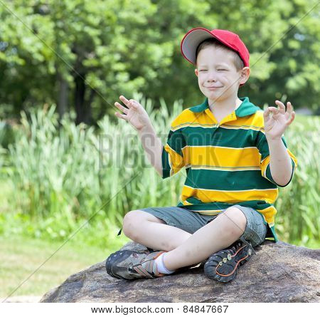 Cute boy with big smile meditating outdoors portrait
