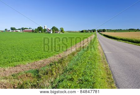 Midwest American farmland with long road and fields