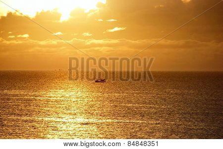 A boat in the golden sea and sky.