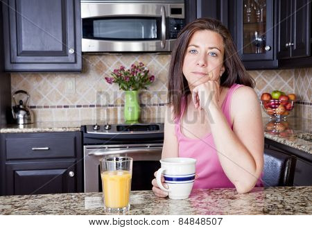 Pretty woman having breakfast in a kitchen