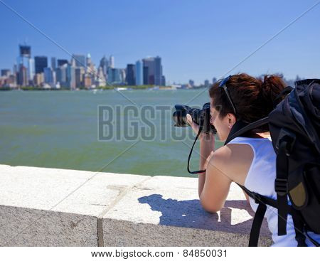 Pretty female photographer taking a picture of New York