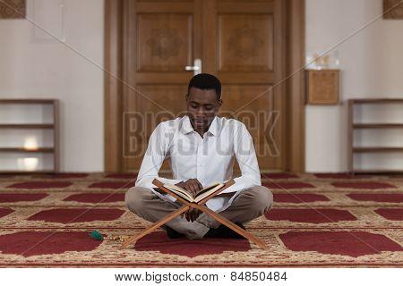 Young African Muslim Guy Reading The Koran