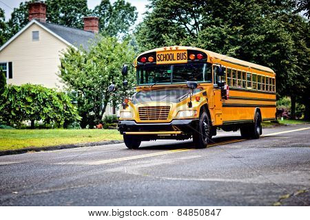 Yellow school bus driving along street
