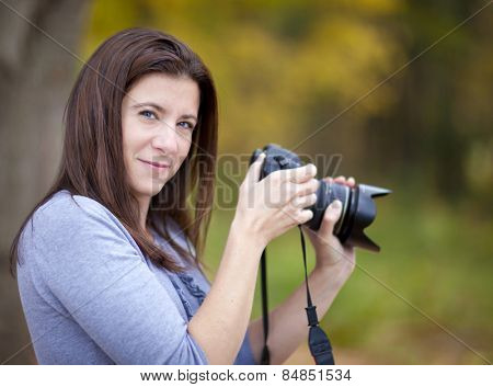 Beautiful smiling woman with camera outdoors in autumn