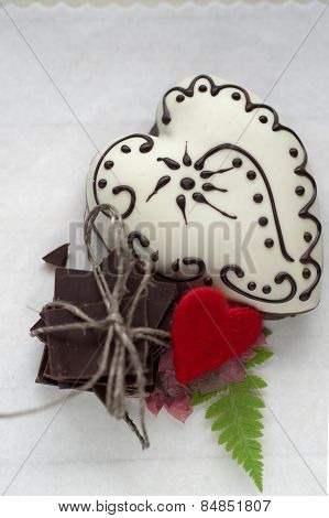 Ginger white heart shaped cookie as a present with pile of chocolate and red felt heart