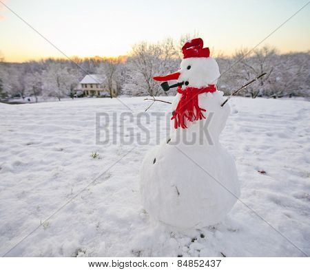 Snowman with red hat and scarf outside at sunset