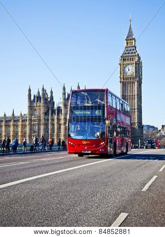 LONDON - DEC 29: Iconic London bus crossing Westminster Bridge in the United Kingdom December 29, 2013 in London, England