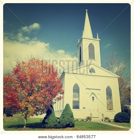 Traditional American white church in the fall with Instagram effect filter