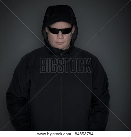 A man wearing hooded jacket and dark glasses criminal theme