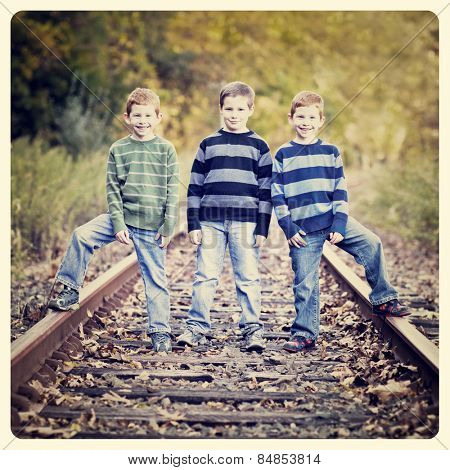 Three brothers standing an old rail tracks with Instagram effect filter