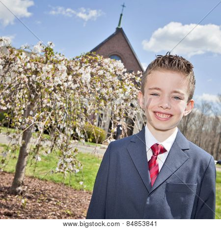 Young handsome boy standing outside a church