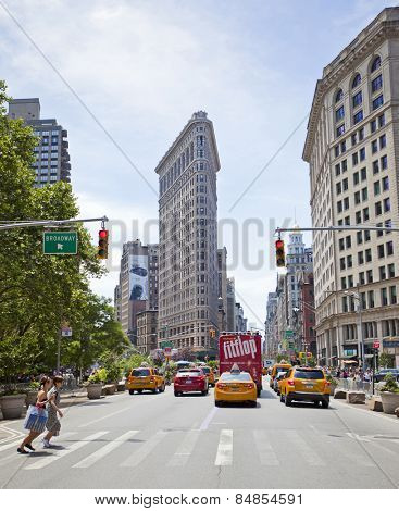 NEW YORK, USA - JUNE 28th 2014: Yellow taxi cab on Broadway in New York City in front of the famous Flatiron building