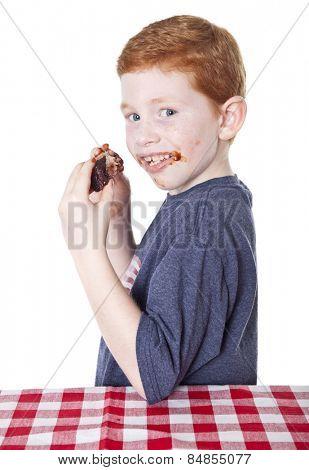 Hungry boy eating BBQ rib in studio
