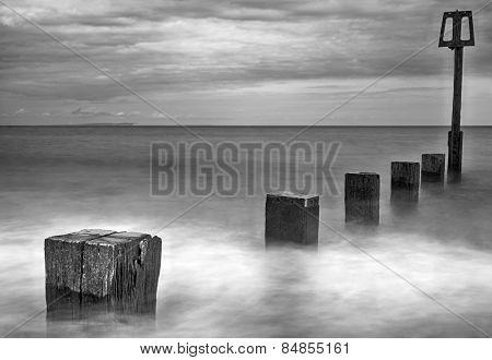 Long exposure of water moving along wooden groynes