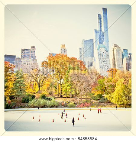 Ice skaters having fun in New York Central Park in fall with Instagram style filter