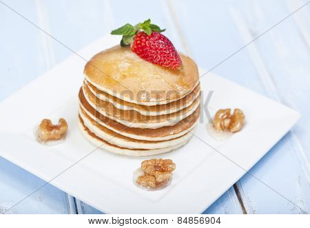 A stack of 6 cooked plain pancakes