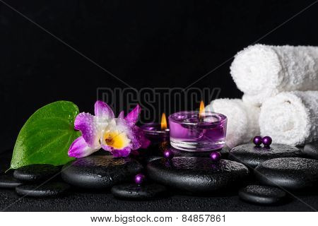 Spa Concept Of Purple Orchid Dendrobium, Leaf With Dew, Towels, Candles And Pearl Beads  On Black Ze