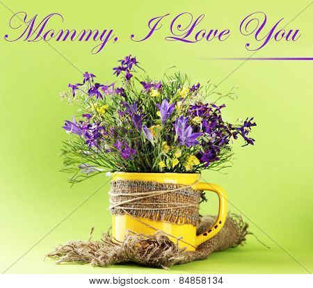 Beautiful wildflowers in cup on bright green background, Mother's Day concept