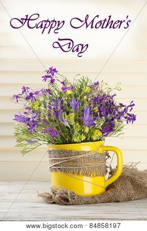 Beautiful bouquet of wildflowers in cup on wooden table