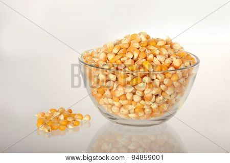 Dried corn in bowl with heap of corn used for making popcorn