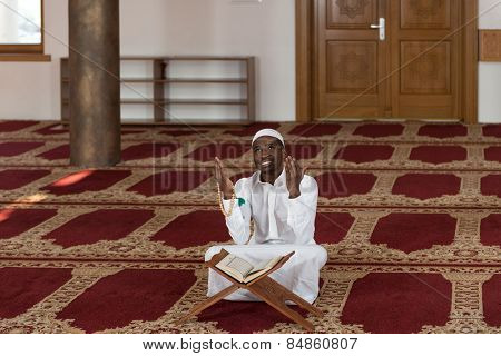 Young African Muslim Guy Reading The Koran