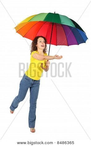 Young Beauty Woman In Yellow Shirt With Multicolored Umbrella Jumping With Reached Out A Hand