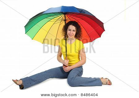 Young Attractive Woman In Yellow Shirt With Multicolored Umbrella Sitting Isolated On White