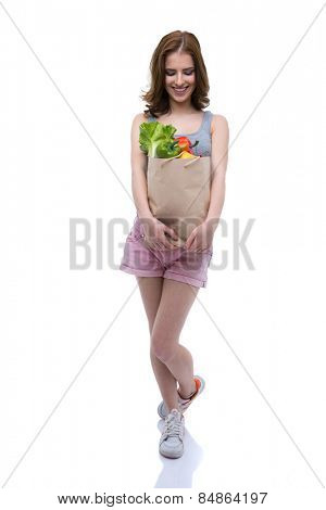 Full length portrait of a smiling woman holding a shopping bag full of groceries