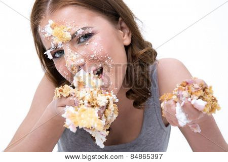 Young cute woman eating cake over white background