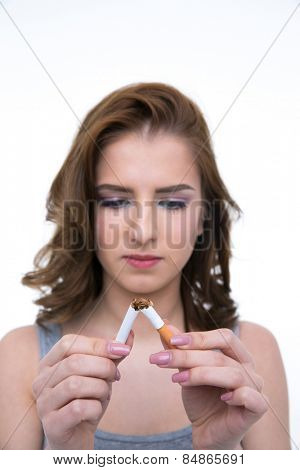 Beautiful woman breaking cigarette and no smoking concept. Focus on cigarette