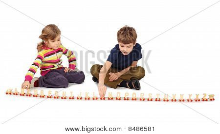 Little Boy And Girl Playing With Wooden Railway Sitting On Floor, Full Body, Train In Line, Isolated