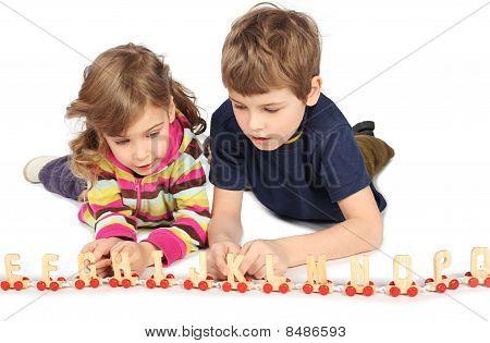 Menino e uma menina brincando com estrada de ferro madeira, deitado no chão, corpo cheio, isolaram no branco