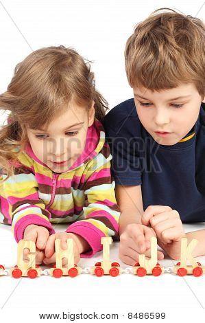 Menino e uma menina brincando com estrada de ferro madeira, deitado no chão, meio corpo, isolado no branco