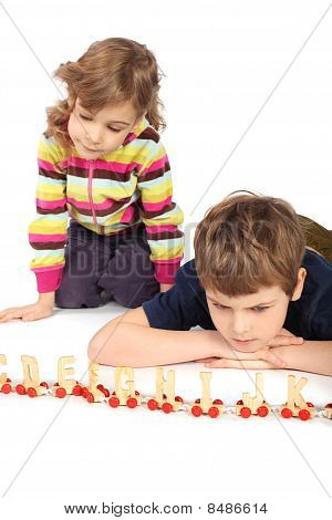 Little Serious Boy And Girl Playing With Wooden Railway, Focus On Boy, Isolated On White