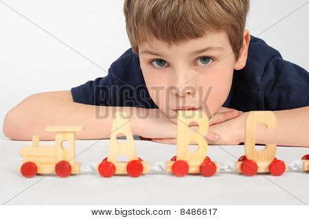 Little Boy Lying On Floor And Playing With Wooden Alphabet Railway