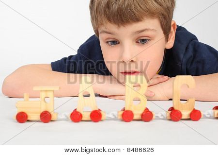 Little Boy Lying On Floor And Playing With Wooden Alphabet Railway, Looking At Train