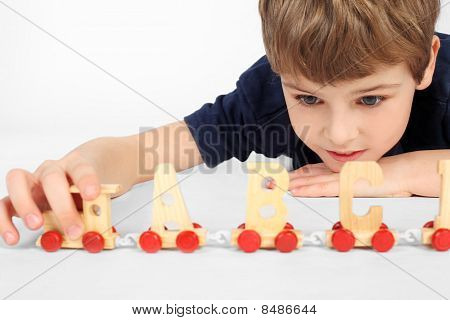 Little Boy Lying On Floor And Playing With Wooden Alphabet Railway, Holding Locomotive