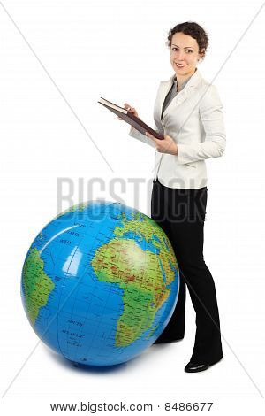 Young Beauty Woman Standing Near Big Inflatable Globe And Holding A Book, Isolated On White