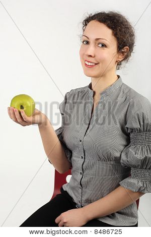 Young Attractive Woman Holding An Apple In One Hand, Looking At Camera