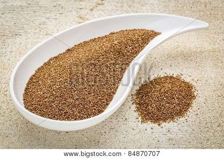gluten free teff grain on a teardrop shaped bowl against white painted grunge wood