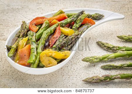 roasted asparagus salad on a teardrop shaped bowl against white painted rustic wood with fresh asparagus