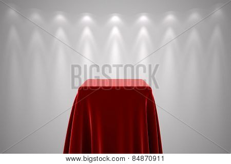 Presentation pedestal covered with a red silk cloth in front of a white wall illuminated by spot lights
