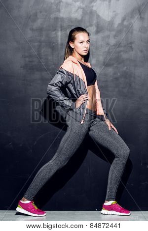 young fitness woman stretching, trained female body, lifestyle portrait, caucasian model