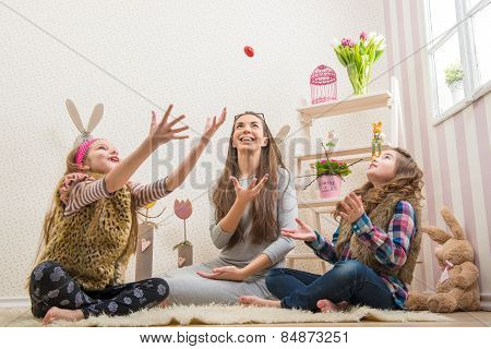 Easter - Mother and two daughters chocolate eggs thrown