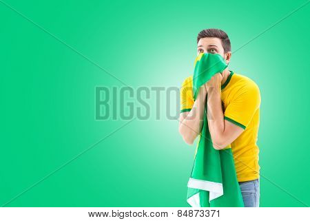 Man looking forward holding the Brazilian flag on Green background