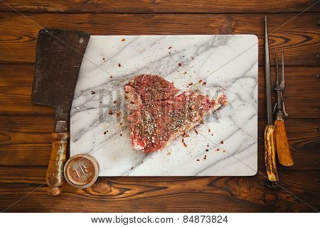 beef steak t-bone with vintage meat fork on marble and old wood backdrop