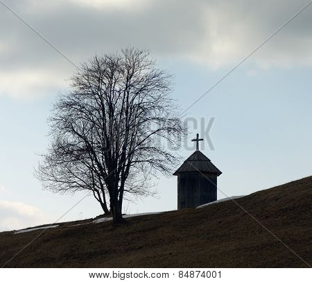 Spring landscape. Wooden chapel and a tree on a hill. Mountain village. Carpathians, Ukraine, Europe