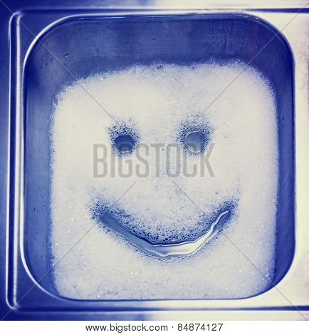 Detergent or soap bubbles and water in the shape of a smiley face in a sink toned with a retro vintage instagram filter effect app or action